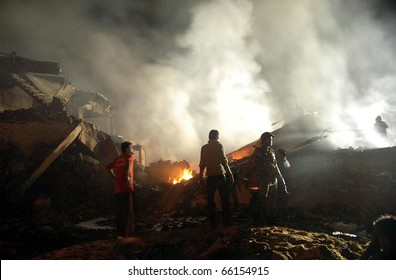 KARACHI, PAKISTAN - NOV 28: People gather in front of burning wreckage of plane at the site of plane crash incident on early morning on November 28, 2010 in Karachi.