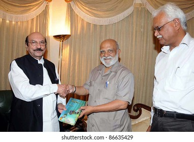 KARACHI, PAKISTAN - OCT 14: Sindh Chief Minister, Syed Qaim Ali Shah receives book from Renowned Intellectual and Journalist, Mehmood Sham during meeting at CM House on October 14, 2011in Karachi, Pakistan.