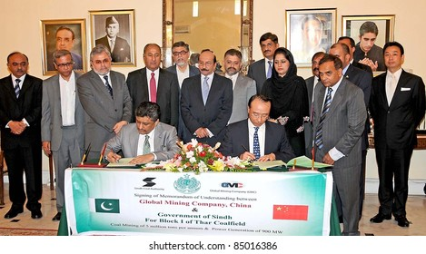 KARACHI, PAKISTAN - SEPT 19: Sindh Coal and Energy Department Sec, Younis Dagha and Liyang Liu CEO of Sino-Sindh Resources of China, sign the MoU for Coal Mining on September 19, 2011 in Karachi, Pakistan.