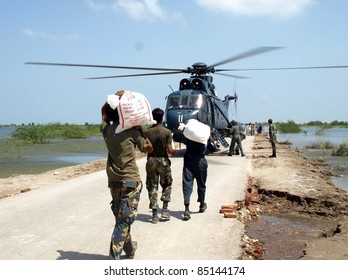 KARACHI, PAKISTAN - SEPT 21: Navy soldiers load relief goods bags for flood affectees on a helicopter for distribute it in flood hit areas of Sindh province September 21, 2011in Karachi.