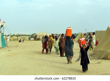 KARACHI, PAKISTAN, SEPT 30: Flood affected woman and child carry drinking water  coolers towards their her make-shift tent houses at flood affectees relief camp established at Hawks bay area on September 30, 2010 in Karachi, Pakistan.
