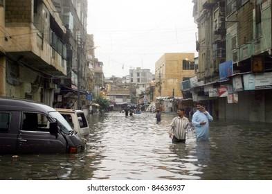 KARACHI, PAKISTAN - SEPTEMBER 13: Rain affected people pass through a flooded area due to heavy downpour of Monsoon Season in Karachi on Tuesday, September 13, 2011.