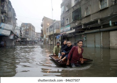 KARACHI, PAKISTAN - SEPTEMBER 13: A rain affected family travels on a push-cart at a flooded area at Burns road due to heavy downpour of Monsoon Season in Karachi September 13, 2011.