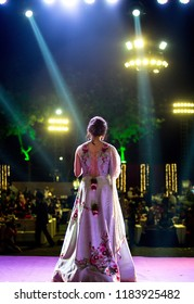 Karachi, Pakistan - September 20 2018: Back of Indian Pakistani Bride wearing silver dress and standing on stage.