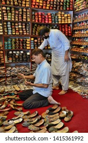 Karachi, Pakistan - September 8, 2016: Stacks of traditional hand made Pakistani khussas line the shelves of a shoe shop. Two shopkeepers, one in a salwar kameez, look for correct sizes and designs.