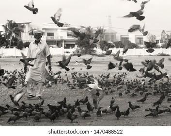 Karachi, Pakistan--May 11, 2019: An unidentified man selling bird feed (bajra) , in an empty plot in Karachi, Pakistan.