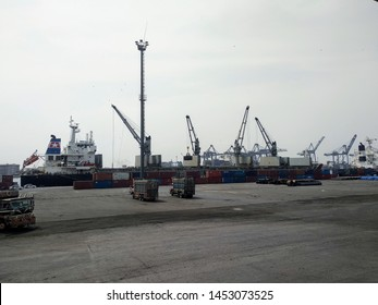 Karachi Port Trust, Karachi , Sindh, Pakistan - July 17 2018: View of gantry cranes unloading / loading a vessel at KPT , also loading trucks in sight.