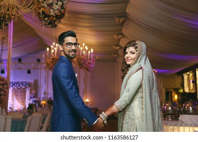 Karachi, Sindh / Pakistan - 01/11/2018 ; Newly wed Indian/ Pakistani bride and groom holding hands and looking back at the camera at their wedding rception