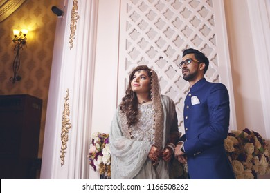 Karachi, Sindh / Pakistan - 01/11/2018 ; Newly wed Indian/Pakistani bride and groom holding hands and looking away from camera at their wedding reception. Both are suited in traditional wedding attire