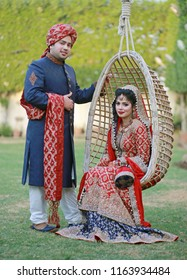 Karachi, Sindh / Pakistan - 12/25/2015; Newly wed desi couple in the garden, groom is wearing a traditional sherwani whereas bride is wearing red bridal dress and sitting on a swing, enjoying the day