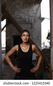 Karachi, Sindh / Pakistan - 17/3/2018 ; Young beautiful, fitness fashion model,  sweating , Image has a dark grungy background. Model has kept her hands on her slim waist wearing black gym attire