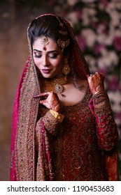 Karachi , Sindh / Pakistan - 4/11/2016 ; Stunning Pakistani / Indian, Desi Bride wearing traditional bridal Jewelry and dress, Holding her duppat and looking down at her wedding