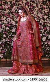 Karachi , Sindh / Pakistan - 4/11/2016 ; Stunning Pakistani / Indian, Desi Bride wearing traditional bridal Jewelry and dress, Holding her dress and her waist looking down, smiling at her wedding