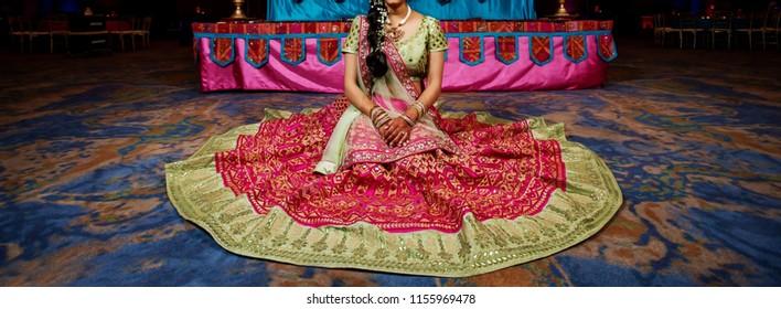 Karachi, SIndh / Pakistan - August 14 2018: Indian / Pakistani Bride spreads her pink and Golden Lehenga / Sharara.
