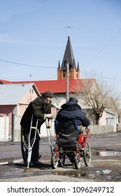 Karaganda Kazakhstan - March 31, 2011: Two disabled people are talking in the street against the background of St. Joseph's Cathedral