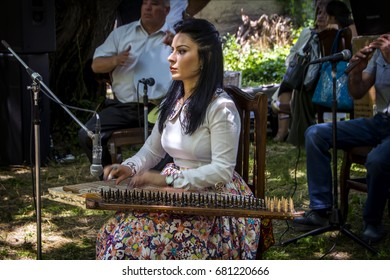 Karahunj, Armenia - July 01, 2017: Armenian girl playing her qanun (kanun, ganoun or kanoon) during Mulberry festival in Karahunj village