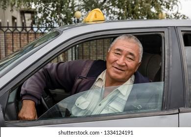 Karakol, Kyrgystan, August 12 2018: Friendly Taxi driver in his old rusty car in Karakol City, Kyrgyzstan