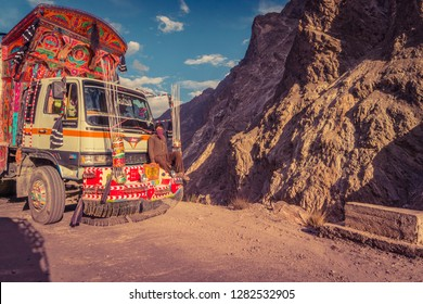 Karakoram Highway, Pakistan - July 19, 2018: Pakistani man traveling on the front bumper of decorated truck on dangerous mountain road. Illustrative editorial.