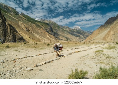 Karakoram, Pakistan - July 24, 2018: Sherpa carrying heavy load in Karakoram Mountain Range in Pakistan. Illustrative editorial.