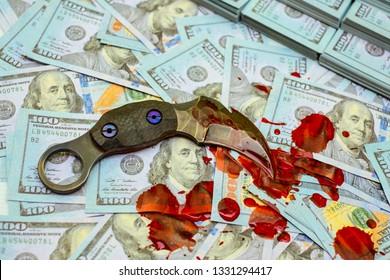 karambit knife on stack bundles of 100 US dollars banknotes bloody