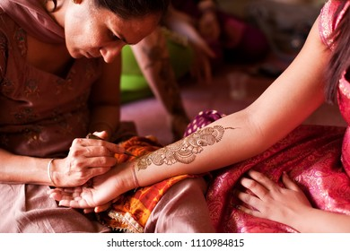 Karamsad, India - 6 February 2011: An unnamed henna artist paints decorative designs, called mehndi, on the arm of a woman in the bridal party at a traditional Indian pre-wedding ceremony.