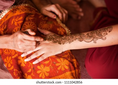 Karamsad, India - 6 February 2011: An unnamed henna or mehndi artist paints intricate designs on the arm of a woman in the bridal party at a traditional Indian wedding event.