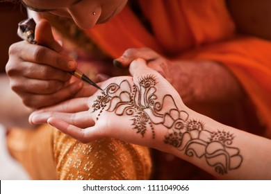 Karamsad, India - 6 February 2011: An artist paints henna designs on the palm of a woman in the bridal party at an Indian wedding event. These tattoos are known as mehndi.