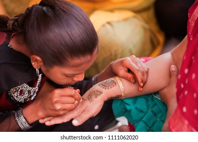 Karamsad, India - 6 February 2011: An traditional Indian artist paints designs on the hand of a member of the bridal party, which last for the duration of the Hindu wedding celebrations.