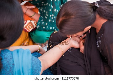 Karamsad, India - 6 February 2011: An unnamed Indian henna artist applies decorative designs, known as mehndi, to the hand of a member of the bridal party at a traditional Hindu pre-wedding event.