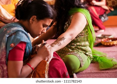 Karamsad, India - 6 February 2011: A unnamed Indian henna artist decorates the hand and arm of a woman in the bridal party before a Hindu wedding.