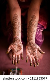 Karamsad, India - 6 February 2011: An unnamed woman from the bridal party at an Indian wedding displays the traditional mehndi designs painted on the palms of her hands and arms.