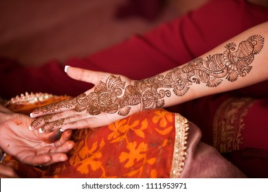 Karamsad, India - 6 February 2011: An unnamed Indian henna artist completes the decoration of the arm of a member of the bridal party at a Hindu wedding event.