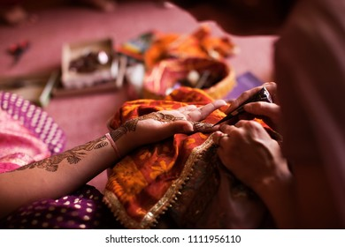 Karamsad, India - 6 February 2011:  An unnamed Indian artist applies henna designs to the hand of a member of the bridal party before a Hindu wedding.