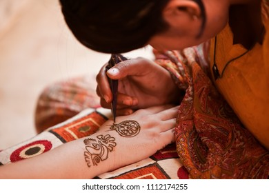 Karamsad, India - 6 February 2011: An unnamed henna or mehndi artist decorates the arm of a woman in the bridal party at a Hindu wedding event.