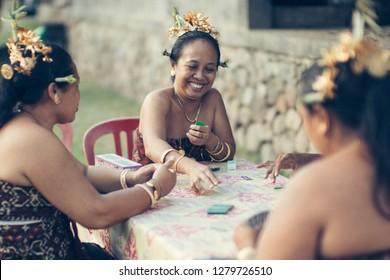 Karangansem, Bali / Indonesia - June 13, 2016 : Woman from Tenganan Village playing card while waiting ceremony begin.