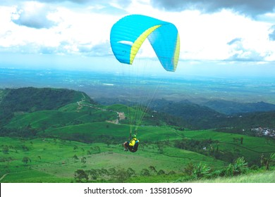 Karanganyar, indonesia - 2nd februari 2019 : a person is paragliding in karanganyar at a cloudy afternoon