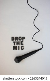 Karaoke microphone and the sentence drop the mic written on a white background