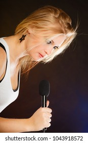 Karaoke, music, singer concept. Blonde woman singing to microphone, performance of young star having fun.