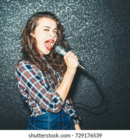 Karaoke Party. Beautiful girl screaming in microphone