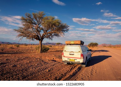 Karas, Namibia - March 30, 2019: Typical 4x4 rental car in Namibia equipped with camping gear and a roof tent driving on a dirt road through Karas Region in Namibia.