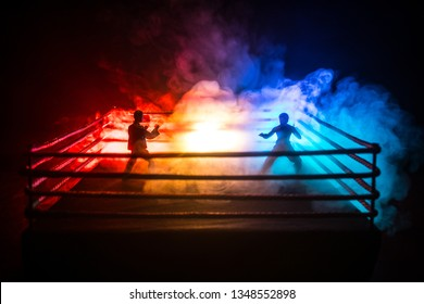 Karate athletes fighting scene on boxing ring with red ropes. Character karate. Posing figure artwork decoration. Sport concept. Decorated foggy background with light. Selective focus