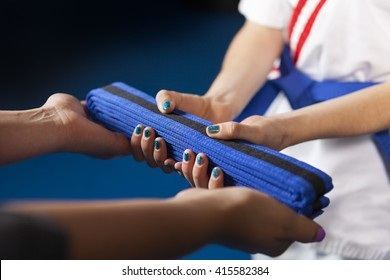 Karate Belt Promotion.  Teacher handing belt to youth student.  Shallow Depth of Field, focus is on the belt.