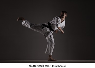 karate boy exercising against dark studio background