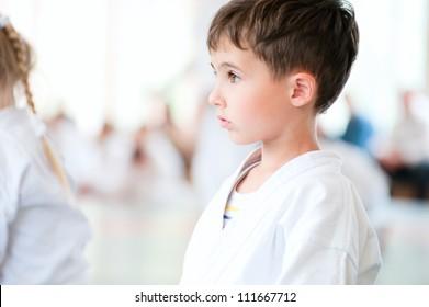 Karate boy profile portrait with children training in sport hall