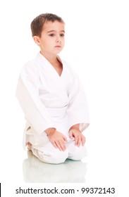 Karate boy sitting in white kimono isolated on white