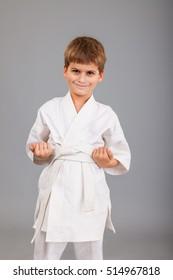 Karate boy in white kimono fighting isolated on gray background