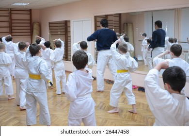 karate boys training in sport hall, focus on left boy in yellow belt