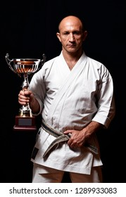 Karate champion hold a trophy cup.