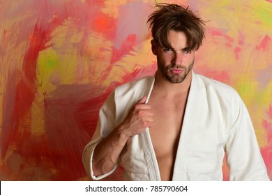 Karate fighter with fit strong body gets ready to fight. Japanese karate training and sports concept. Man with serious face and bristle on colorful background, copy space. Guy poses in white kimono.