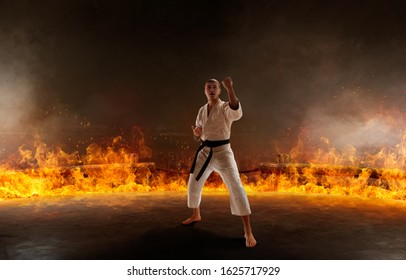 Karate fighter on fire background.